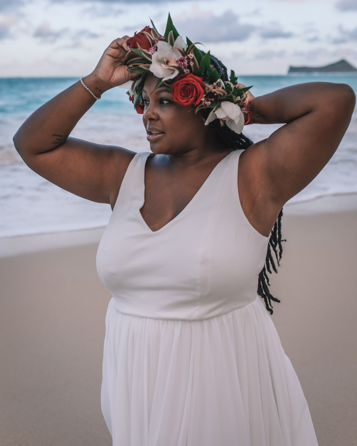 A young Black female stands on a beach, with a crown of tropical flowers on her head