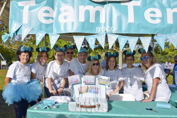 Liz's Mouseketeals gather at an outdoor team table at an ovarian cancer fundraiser