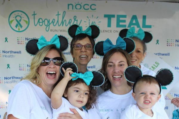 Four women and kids wearing Mouseketeer ears with teal ribbons to raise ovarian cancer awareness