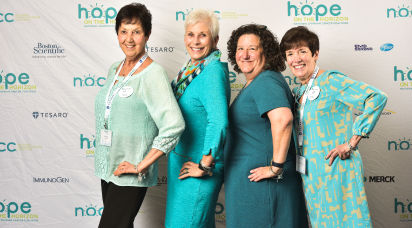Four females pose in front of an NOCC background