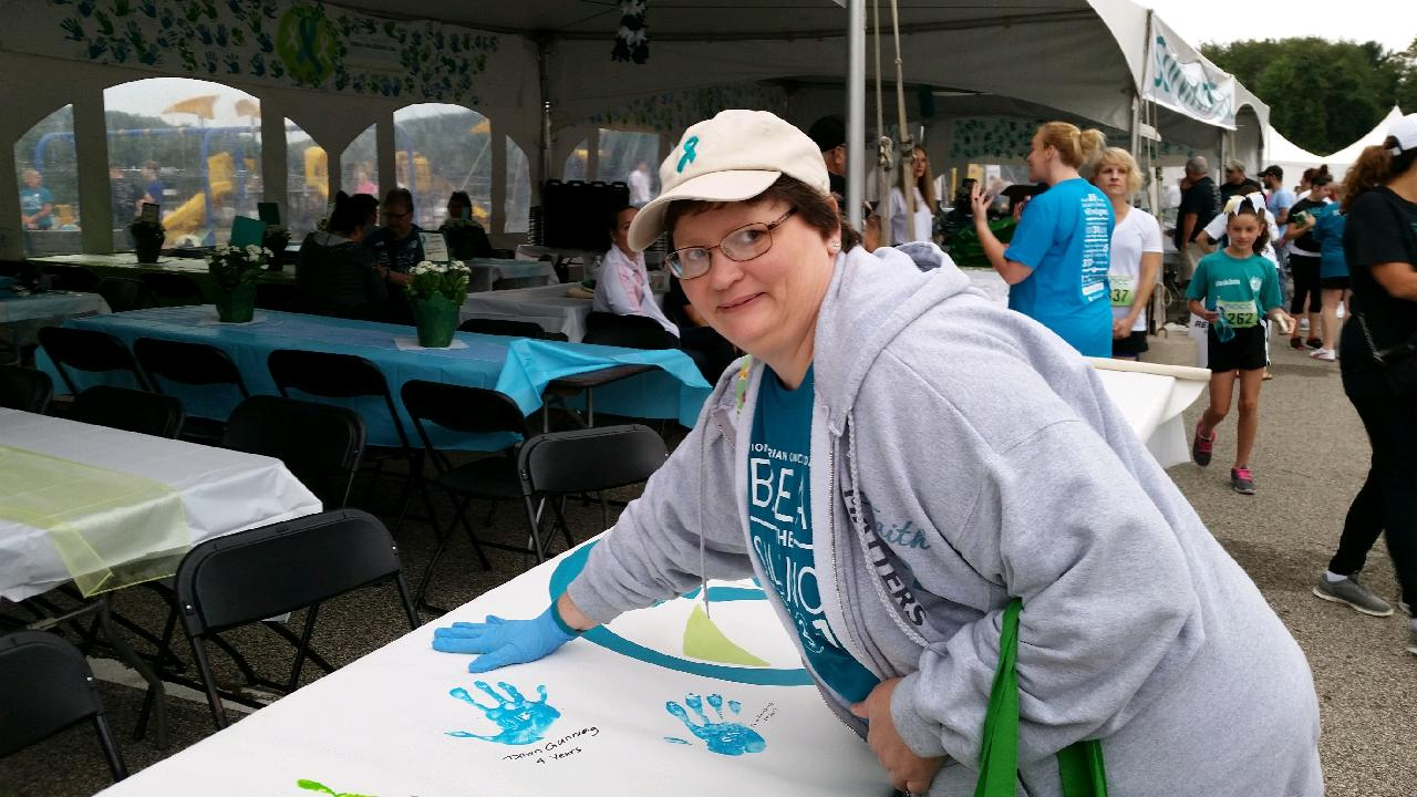 A survivor in a baseball cap with a teal ribbon logo leaves a teal handprint on a poster