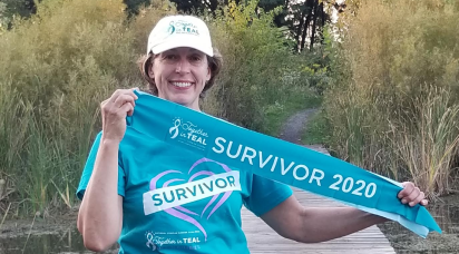 A female proudly holds a survivor 2020 sash