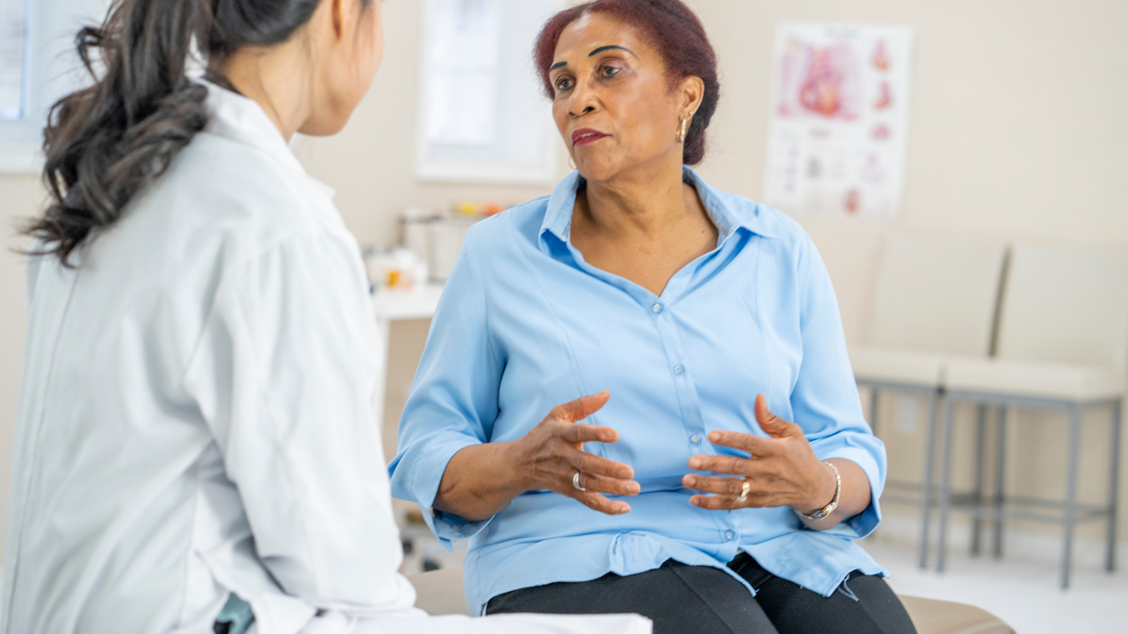 A middle-aged Black female talks to her female physician